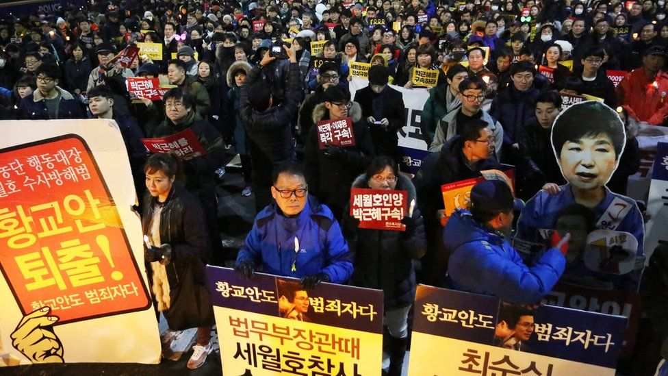 """South Koreans march carrying placards reading """"Park Geun-Hye and Prime Minister Hwang Kyo-ahn Out"""""""