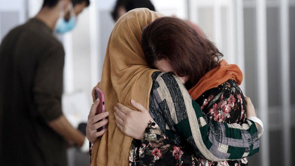 A woman embraces her sister-in-law as she arrives with other Afghan refugees