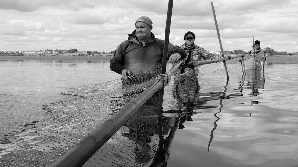 Fishermen in the water, black and white photo