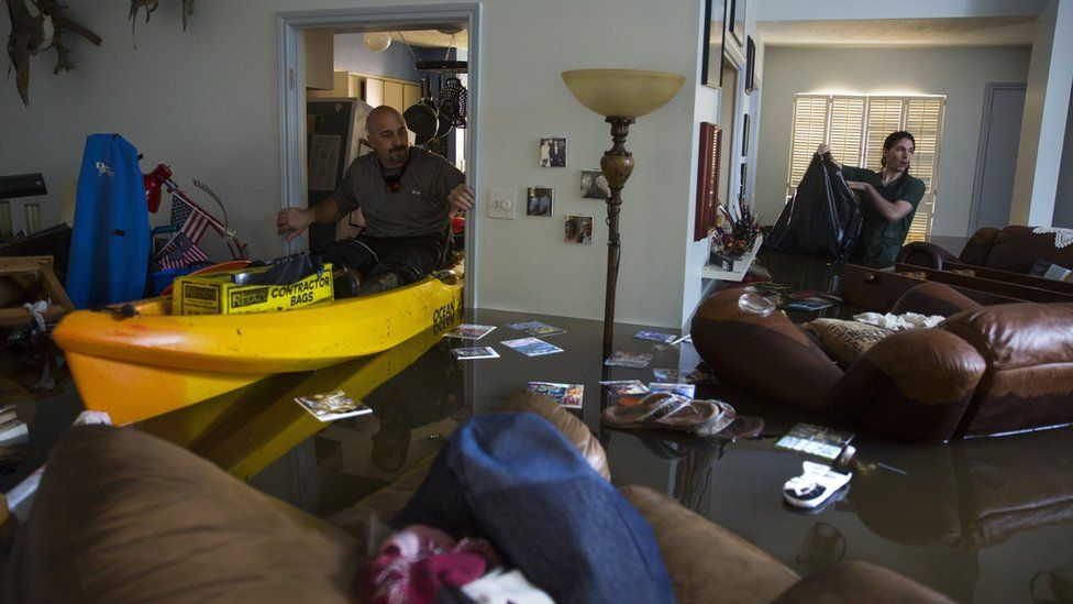 """arry Koser Jr. (L) and his son Matthew look for important papers and heirlooms inside Larry Koser Sr.""""s house after it was flooded by heavy rains from Hurricane Harvey August 29, 2017 in the Bear Creek neighborhood of west Houston, Texas."""