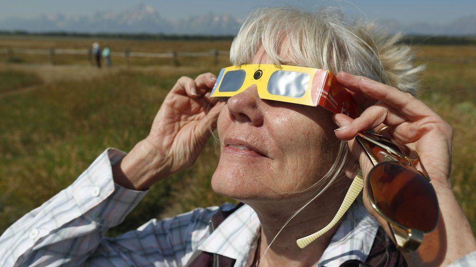 Penny Farster-Narlesky of Denver Colorado test her solar eclipse glasses at an roadside information center in Grand Teton National Park on August 20, 2017 outside Jackson, Wyoming.