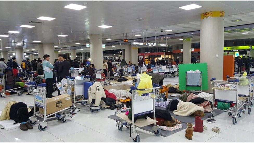 A photo taken with a smart phone camera shows passengers sleeping in a departure hall at Jeju International Airport, in Jeju, South Korea, early 25 January 2016
