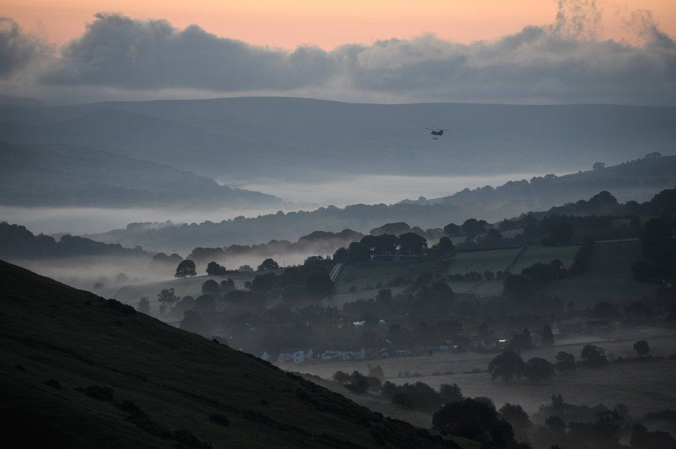 Helicopter flies in over misty valley