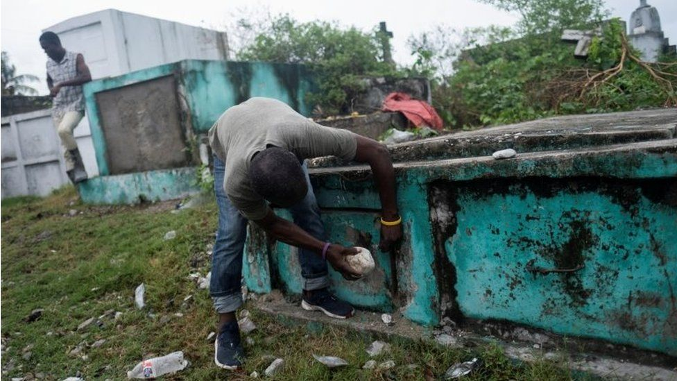 """A man opens a grave to bury a victim of Saturday""""s 7.2 magnitude quake, in Les Cayes, Haiti August 17, 2021"""