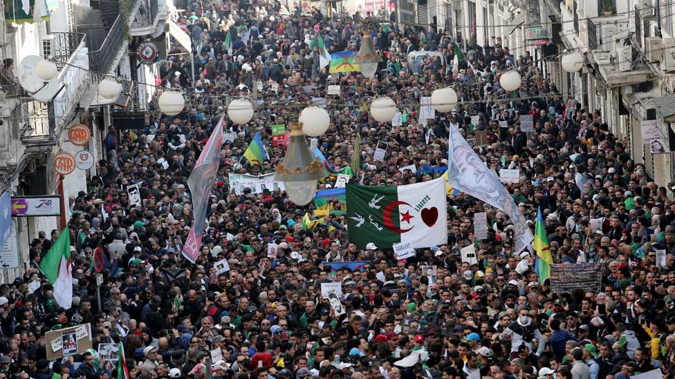 Algerians carry banners and flags during a demonstration to mark the first anniversary of protests that ousted President Abdelaziz Bouteflika, in Algiers, Algeria February 22, 2020.
