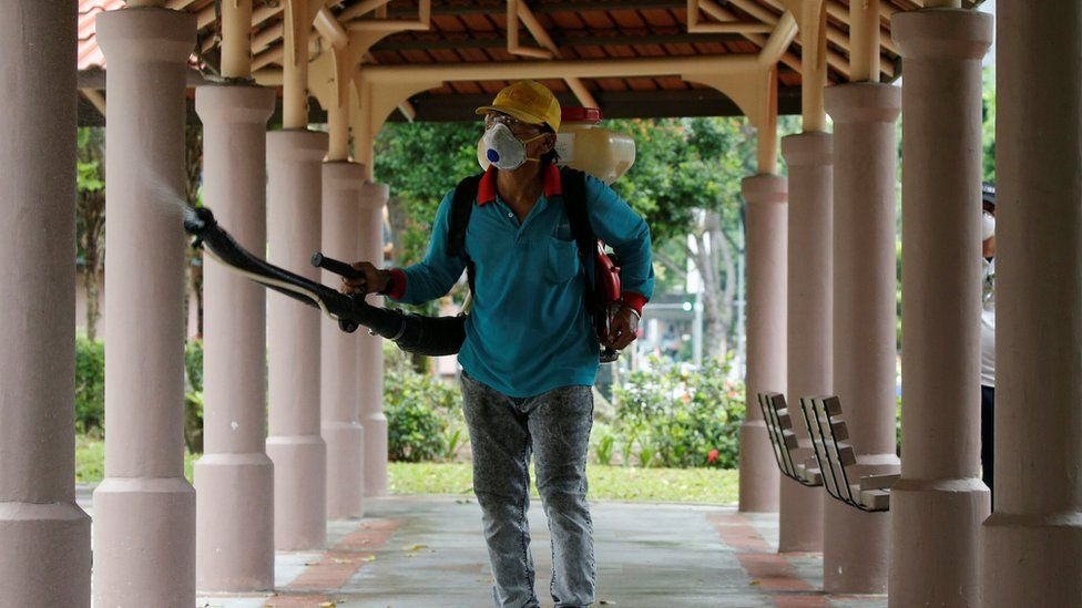 A worker sprays insecticide outside a housing block in Singapore on 30 August 2016