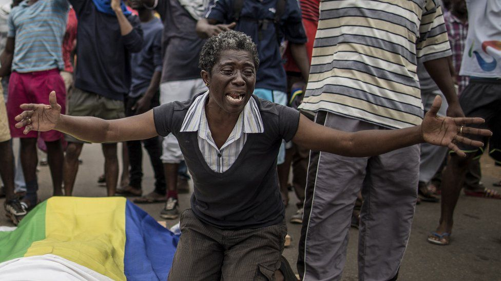 A woman cries over the body of Axel Messa, 30, wrapped in the flag of Gabon after he was shot in front of his home, 2 September 2016