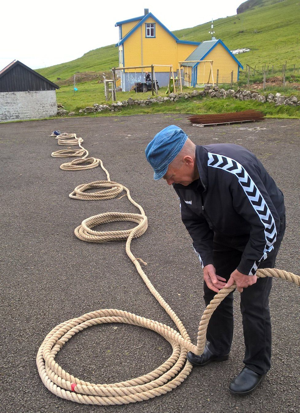 Oscar Joensen lays out the long rope needed for the climb before the village school
