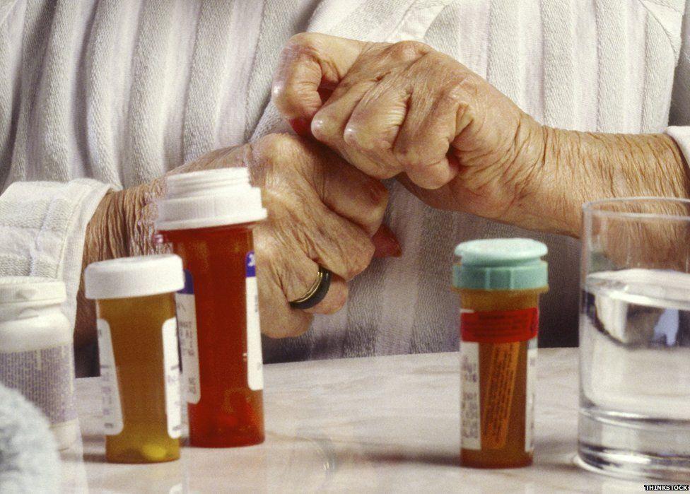 An elderly person opening a bottle of pills