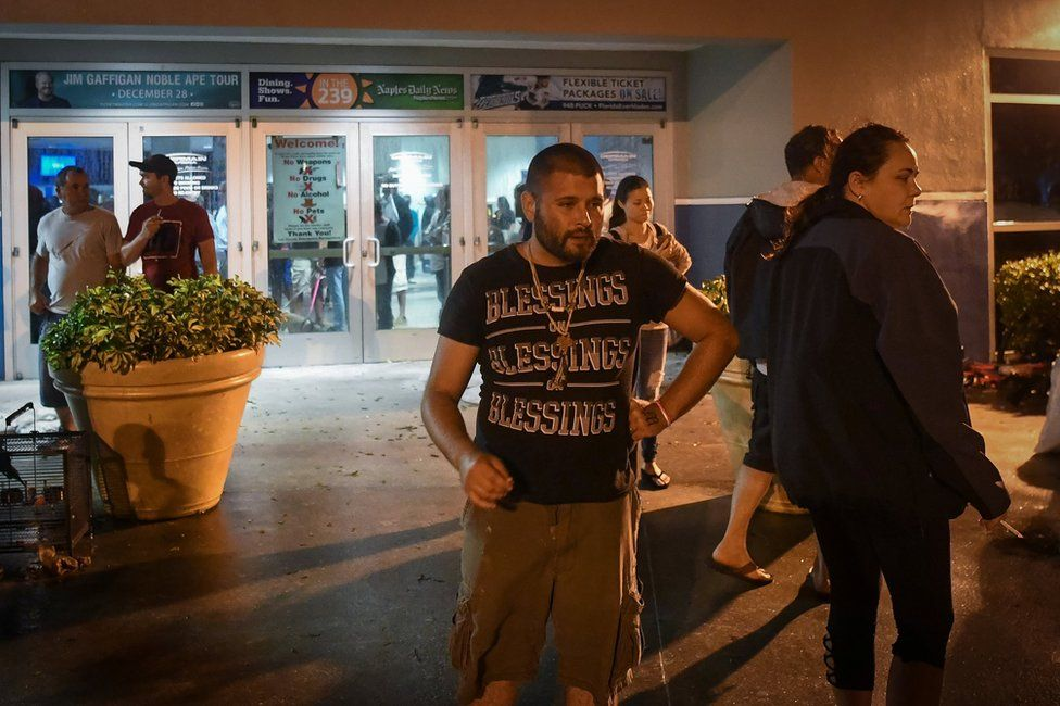 People smoke cigarettes outside the Germain Arena, a facility used to shelter local residents during hurricane Irma in Estero, Florida, 10 September