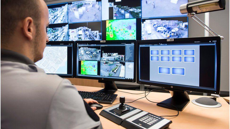 policeman watching surveillance monitors in Geneva
