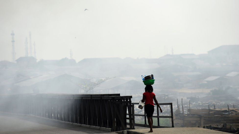 A woman walks through the smoke emitted from a dump