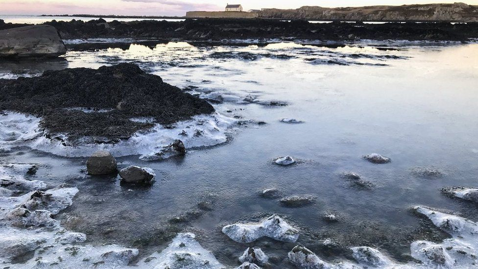 Frozen sea at Porth Cwyfan bay on Anglesey
