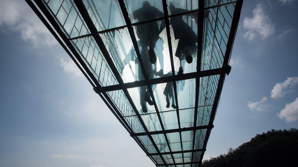 Chinese tourists walk across a glass-bottomed suspension bridge in the Shiniuzhai mountains in Pingjiang county, Hunan province