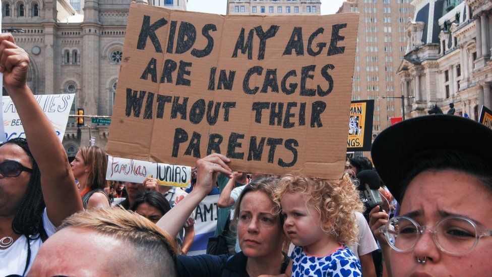 Protesters, with a small child, holding a sign saying 'kids my age are in cages without their parents'