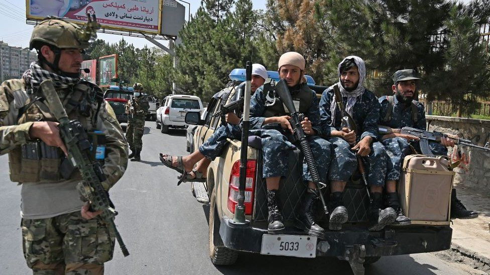 """Taliban Fateh fighter, a """"special forces"""" unit, stands guard along with other fighters on a street in Kabul"""