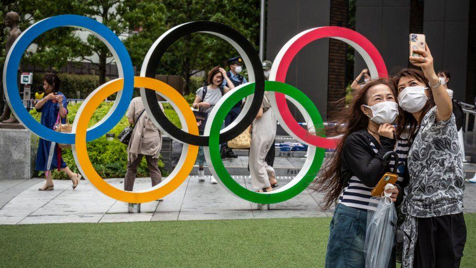 People take selfie with Olympics rings on July 27, 2021 in Tokyo, Japan.