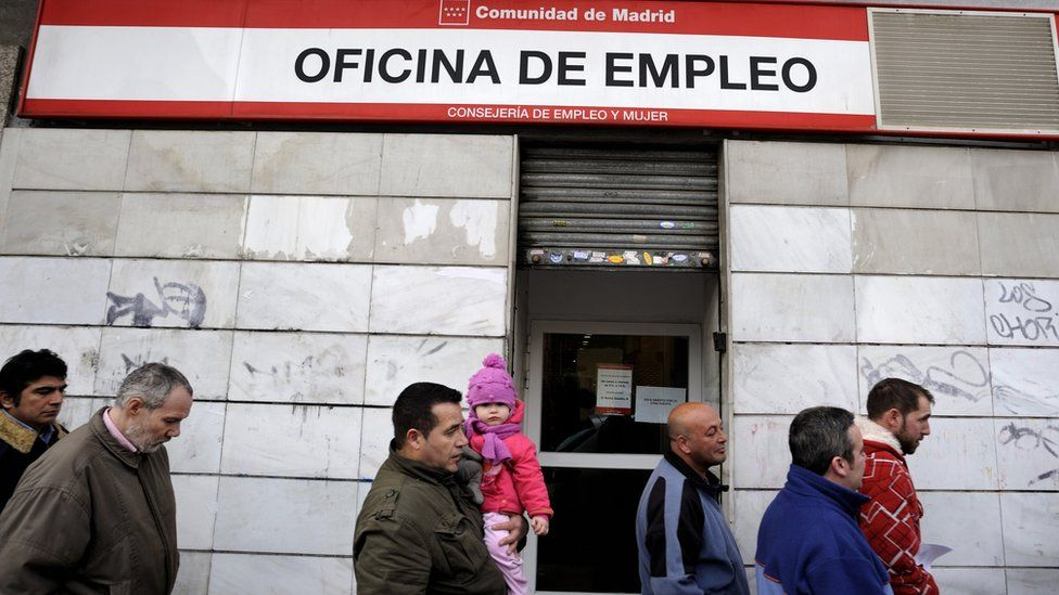 People wait in line to enter a government job centre in Madrid