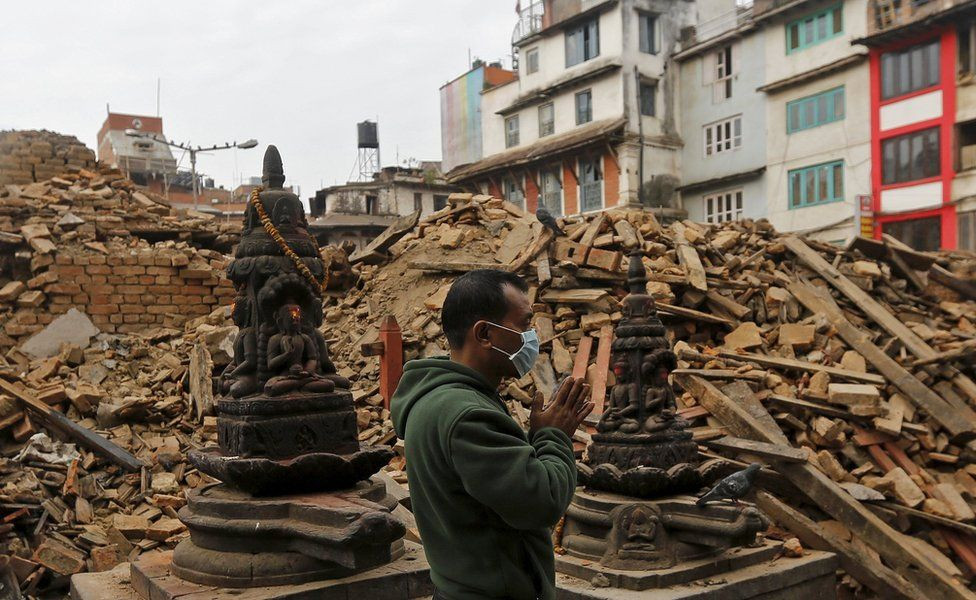 A man prays next to the rubble of a temple, destroyed in the April 2015 earthquake in Kathmandu