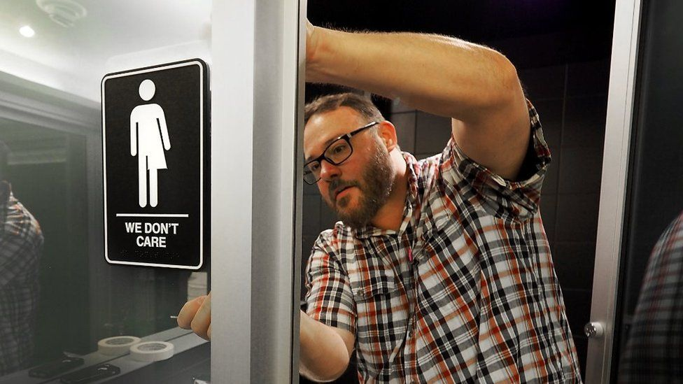 Picture of a man putting up the gender neutral bathroom signs