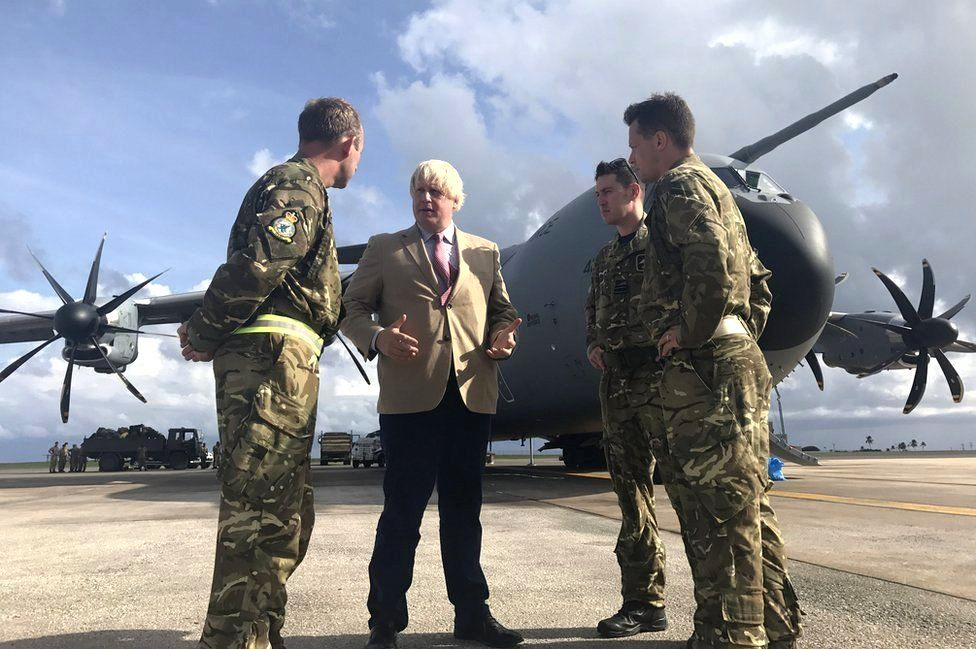 Boris Johnson talks to pilots in front of an aircraft.