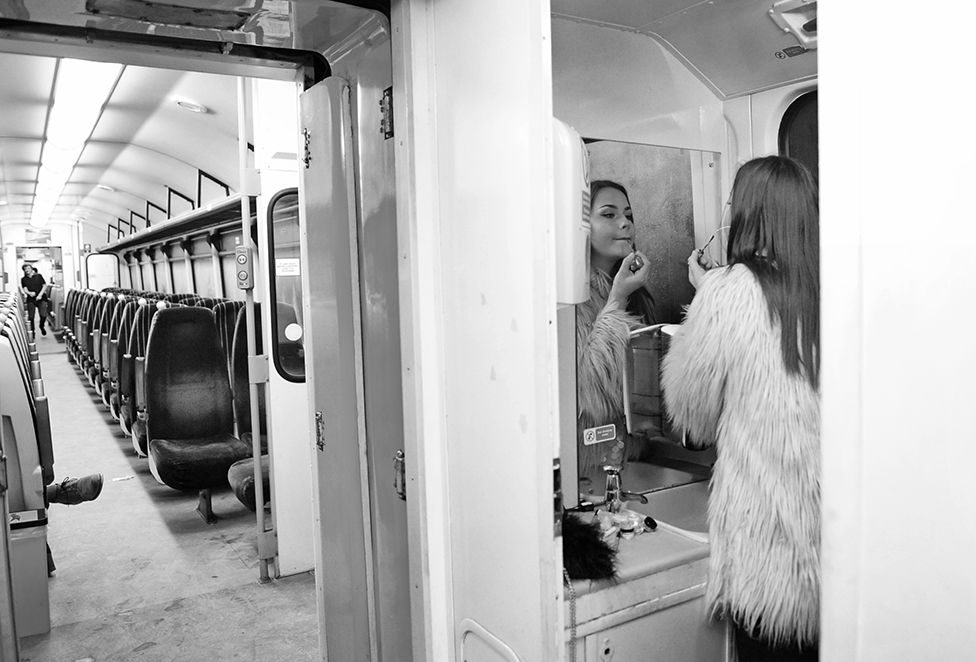 A woman puts on her lipstick in a train toilet