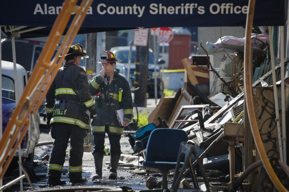 Firefighters work on the scene following an overnight fire that claimed the lives of at least nine people at a warehouse in the Fruitvale neighborhood on December 3, 2016 in Oakland, California