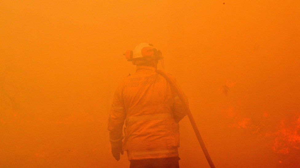 A firefighter seen among the thick smoke and orange light of a bushfire near Sydney