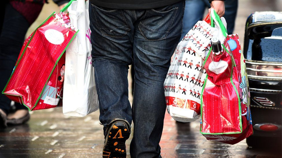 A man is seen carrying multiple bags of Christmas shopping
