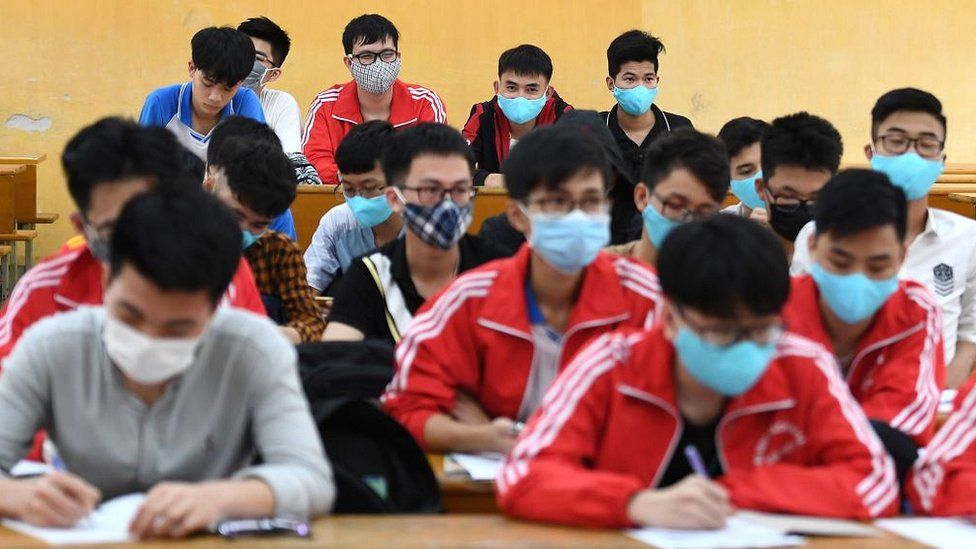 Students, wearing facemasks amid concerns of the COVID-19 novel coronavirus outbreak, study inside a classroom at the University of Science and Technology in Hanoi
