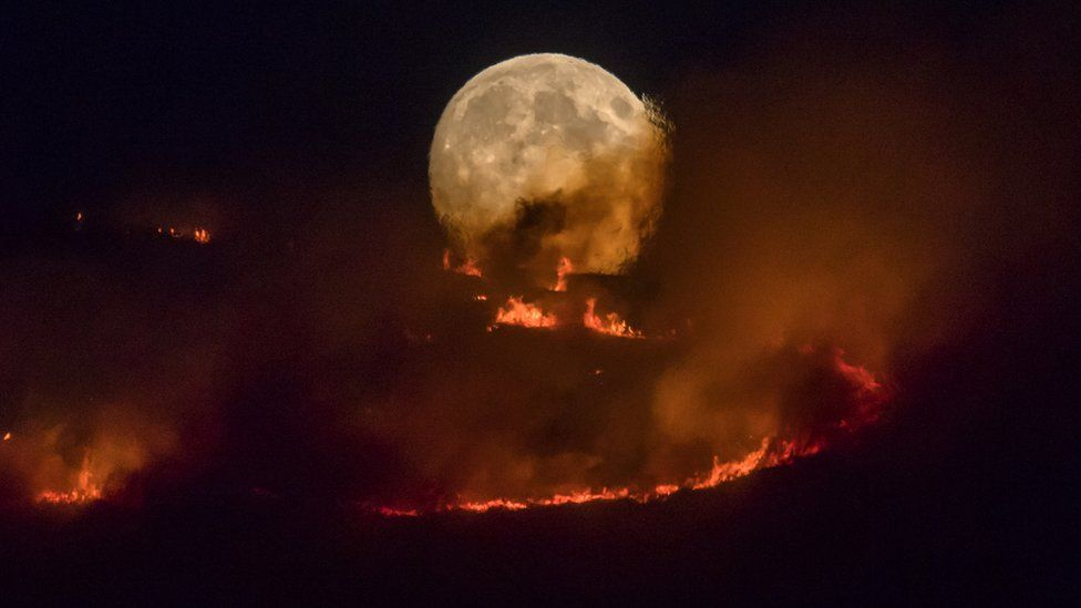 The full moon rises behind burning moorland as a large wildfire sweeps across the moors between Dovestones and Buckton Vale in Stalybridge, Greater Manchester on 26 June 2018 in Stalybridge, England.
