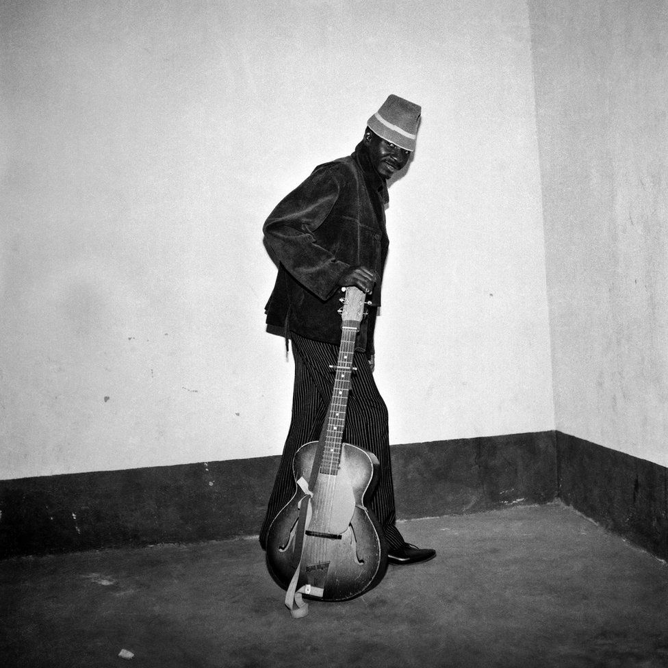A man posing with a guitar