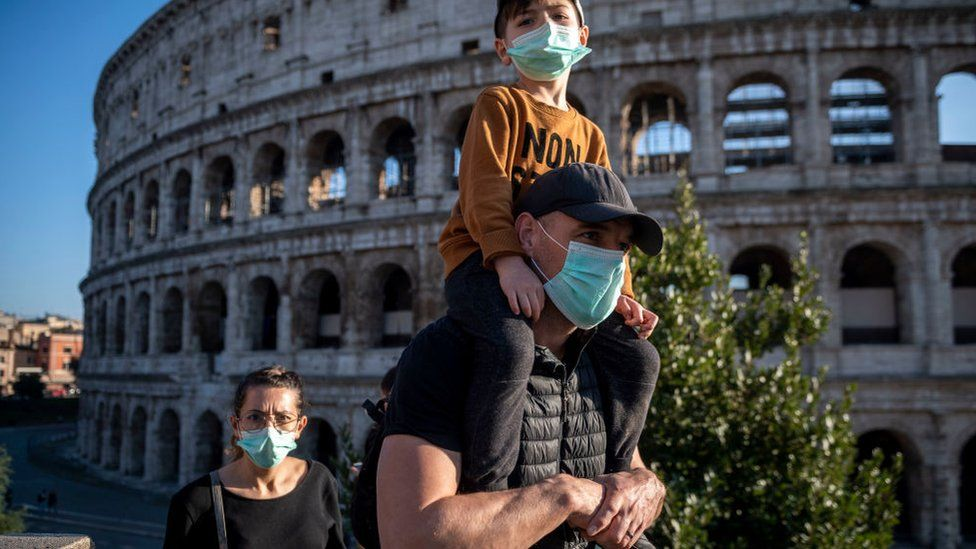: Tourists wearing face masks visit the Colosseum area on February 24, 2020 in Rome, Italy. The Italian government declared a state of emergency on January 31 and today the coronavirus (Covid-19) has claimed its sixth victim in Italy, an 80-year-old man from Castiglione d'Adda who died in Milan's Sacco Hospital