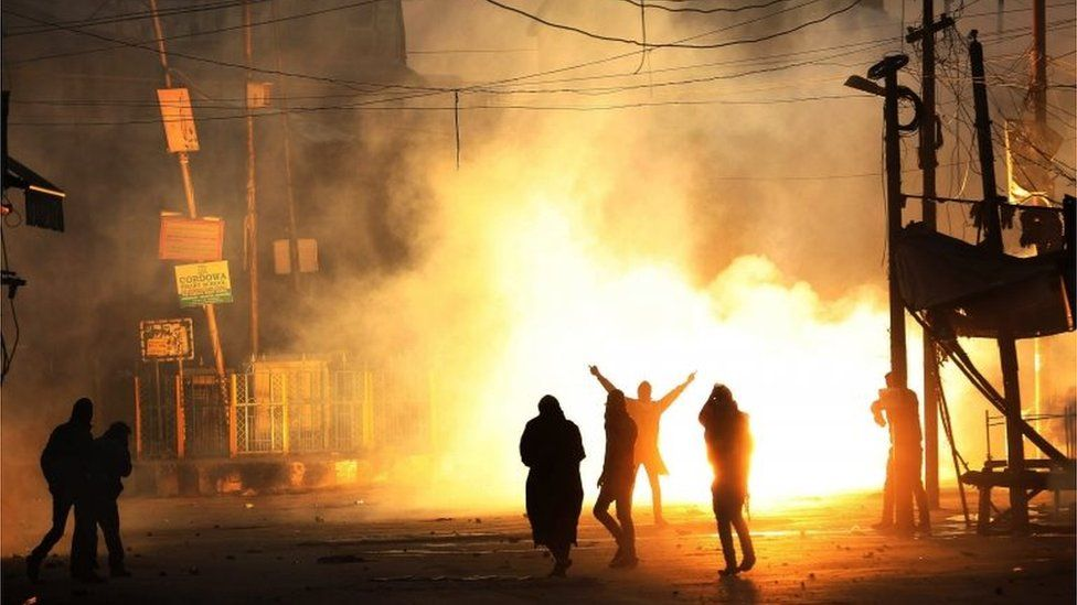 Kashmiri Muslim protesters shout slogans amid exploding smoke canisters fired by the Indian security forces during a protest in downtown of Srinagar, the summer capital of Indian Kashmir, 04 December 2015