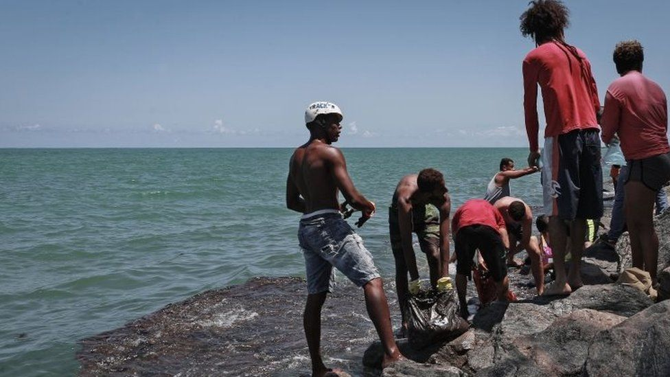 People remove crude spilled in Paulista, Pernambuco state, Brazil. Photo: 23 October 2019