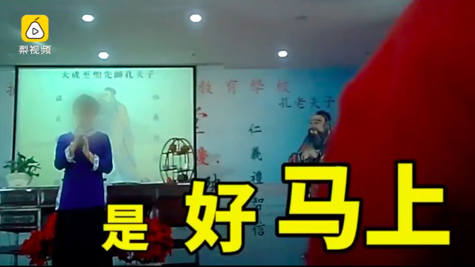 Screenshot of a Pear Video showing a female lecturer standing in front of the class.