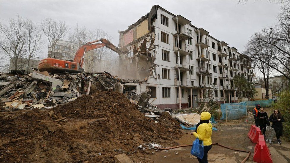 A women watches as excavator and workers demolish a five storey khrushchyovka building in Moscow