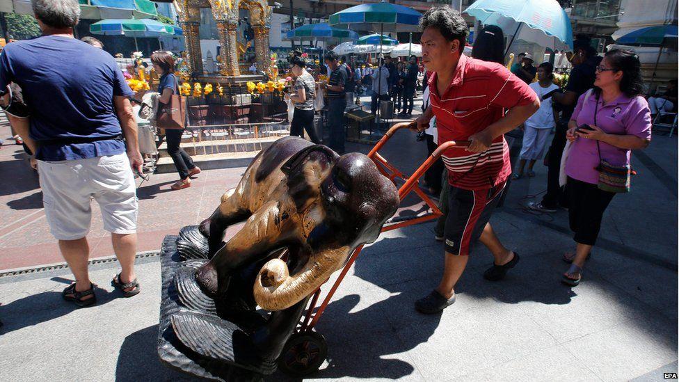 Shrine workers move elephant statues as tourists return