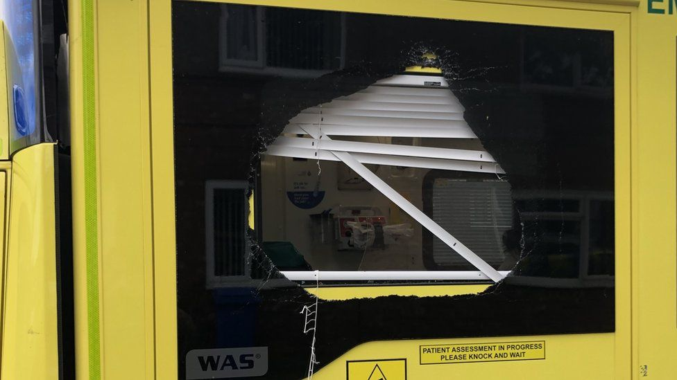 A smashed side window on one of the ambulances