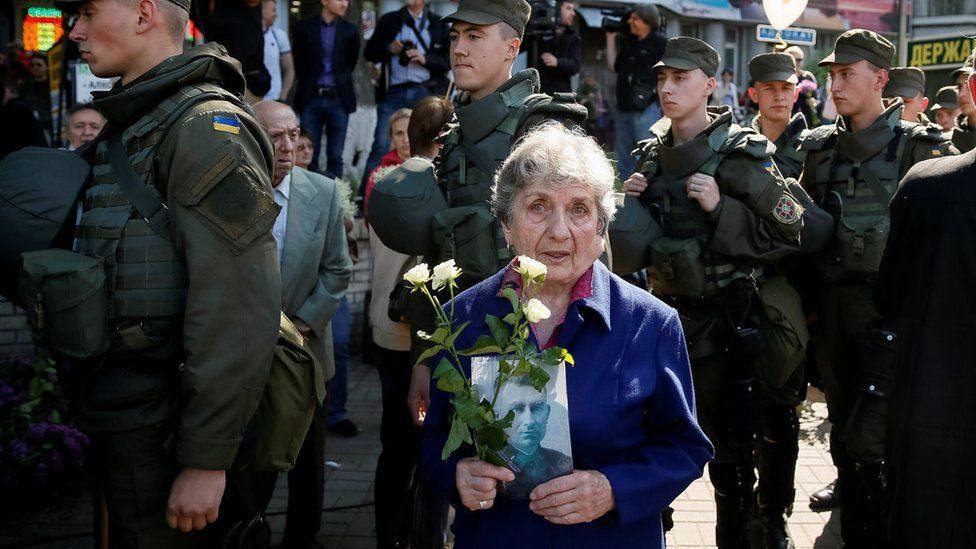 A woman carries a picture of a World War Two participant as she takes part in the Immortal Regiment march during the Victory Day celebrations, marking the 71st anniversary of the victory over Nazi Germany in World War Two, in central Kiev, Ukraine, May 9, 2016.
