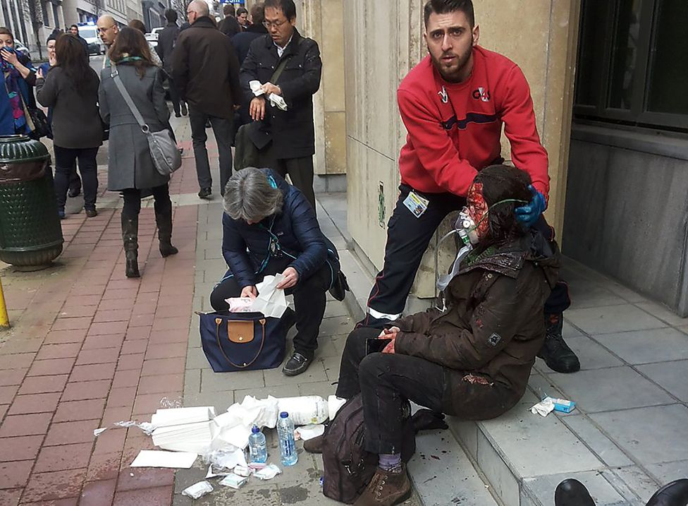 A private security guard helps a wounded women outside the Maalbeek - Maelbeek metro station in Brussels on March 22, 2016 after a blast at this station located near the EU institutions.
