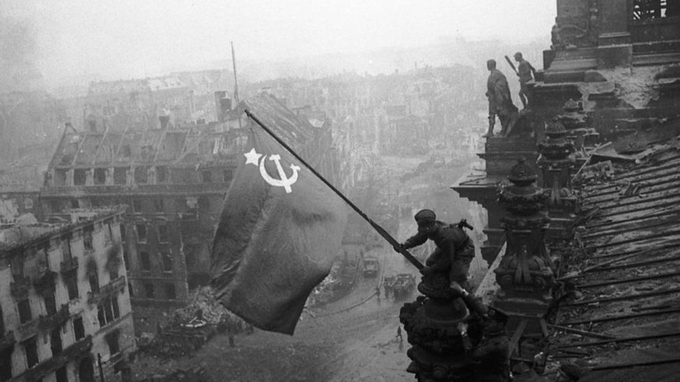 A Soviet soldier pictured hoisting a flag over the Reichstag in 1945