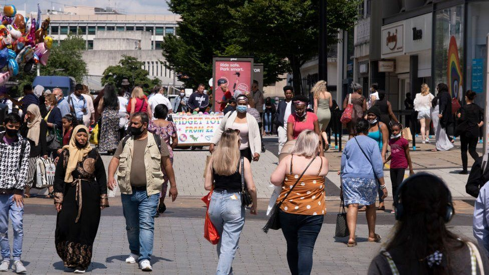 Shoppers in Birmingham city centre, some with and some without face coverings.