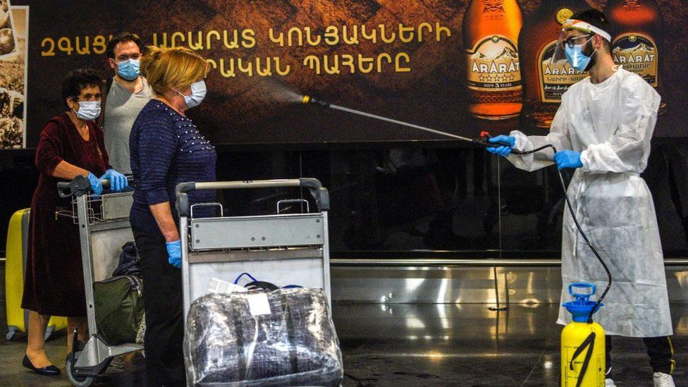 Health workers spray airport arrivals in Yerevan, Armenia