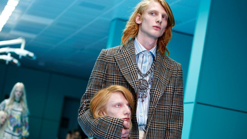 Male model walks down the catwalk holding a mannequin head that is a replica of his head