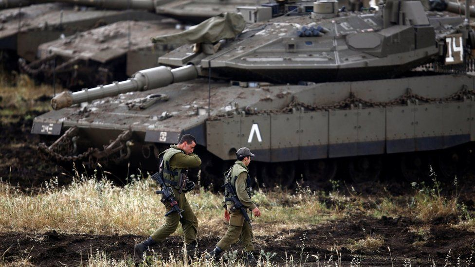 Israeli soldiers walk next to tanks near the Israeli side of the border with Syria in the Israeli-occupied Golan Heights, Israel May 9, 2018