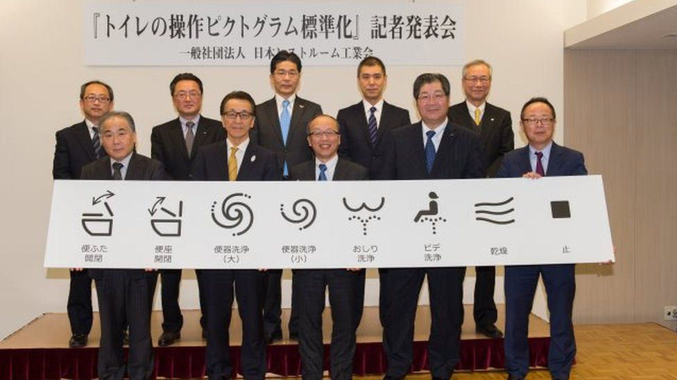 Senior members of the association hold up the new symbols, which are, from left, raise the lid, raise the seat, large flush, small flush, rear spray, front spray, dry, and stop