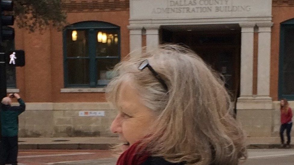 Toni Glover in Dealey Plaza, Dallas, with the Book Depository building in the background