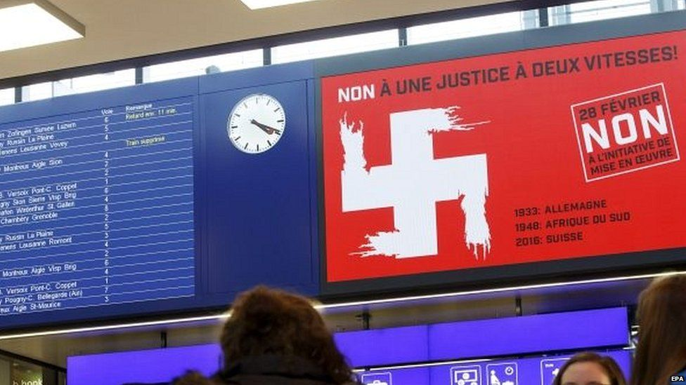 Campaign advert shows montage of the white cross of the Swiss national flag and the Swastika symbol, at a Geneva train station 23/02/2016