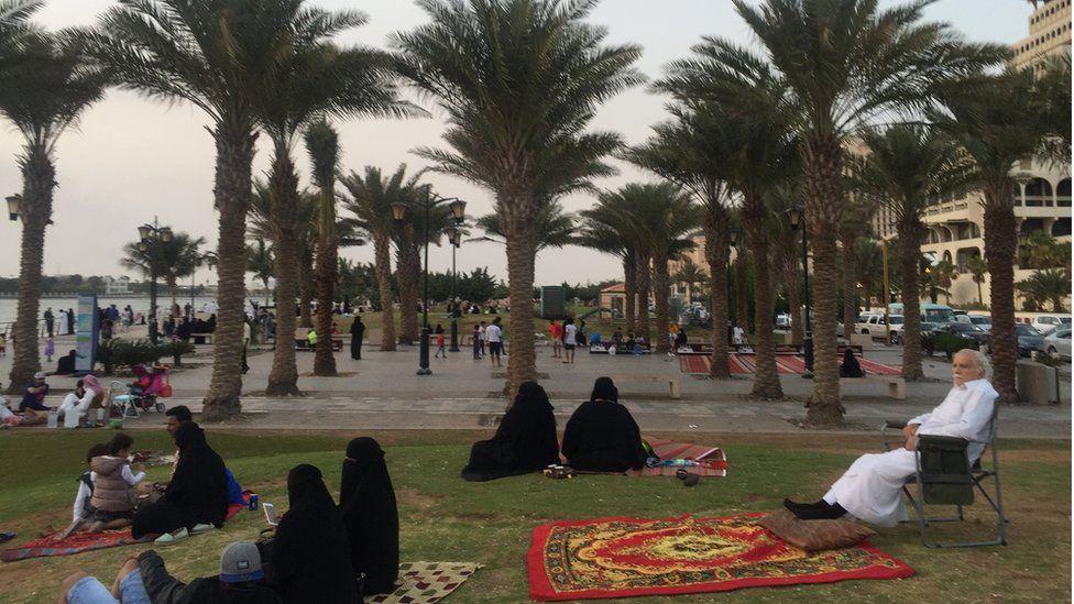 Saudis relax on outdoors, sat on the grass beneath trees